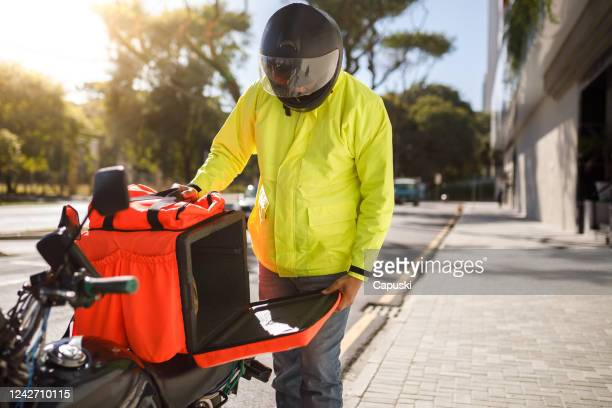 delivery biker open his delivery backpack - motoboy - crash helmet stock pictures, royalty-free photos & images