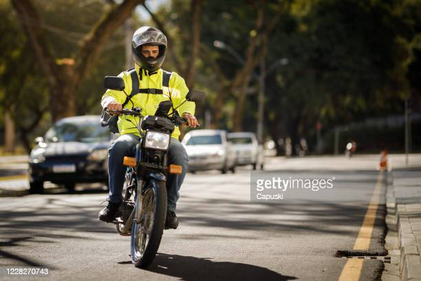 motociclista entregador andando pela rua - motoboy - motocicleta - fotografias e filmes do acervo