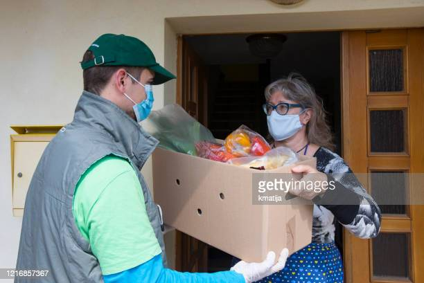 delivery boy delivering groceries to front door of a mature woman during coronavirus quarantine - prevention stock pictures, royalty-free photos & images
