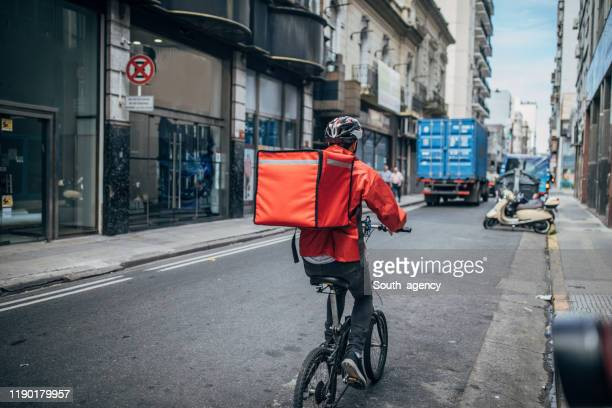 delivery boy on bicycle in city - delivery person stock pictures, royalty-free photos & images