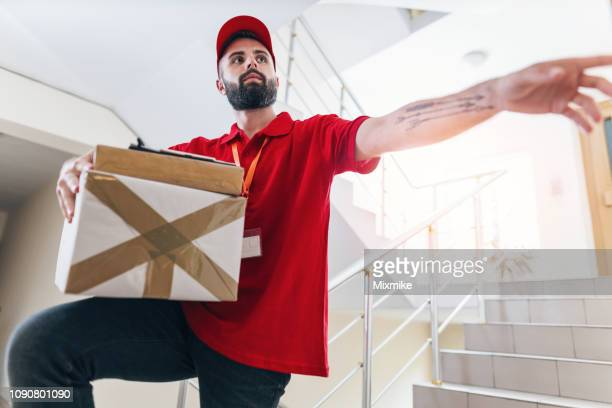 delivery boy ringing on the doorbell - ringing doorbell stock pictures, royalty-free photos & images