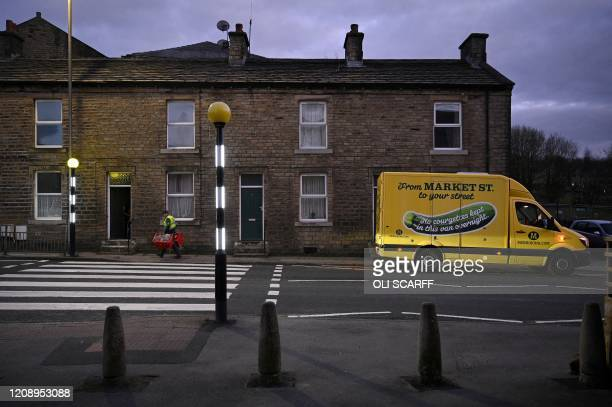 Delivery driver carries baskets of food as he delivers an online shopping order to a resident, from the supermarket Morrisons, in Marsden, northern...