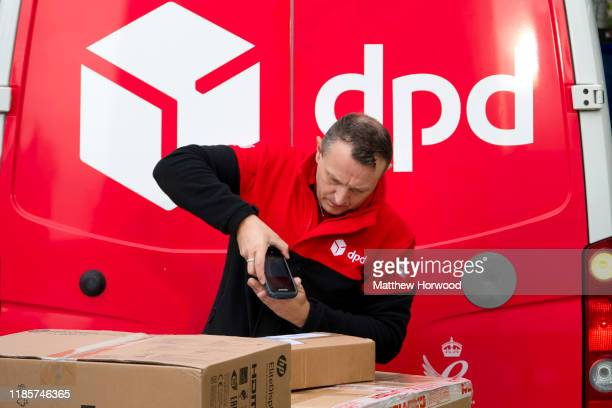 Delivery driver scans a parcel in front of a DPD branded delivery van on October 30, 2019 in Cardiff, United Kingdom.