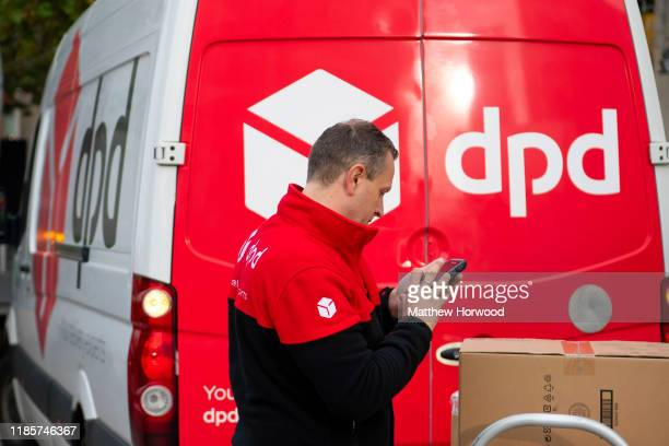 DPD delivery driver scans a parcel in front of a DPD branded delivery van on October 30 2019 in Cardiff United Kingdom