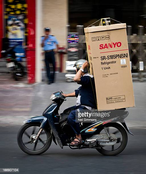 CONTENT] A delivery driver uses one hand to hold on to a fridge he is delivering on his motorbike in Ho Chi Minh City in Vietnam There is a 4pack of...