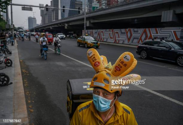 A delivery driver wears a protective mask as he waits to drop a food order during rush hour on July 17 2020 in Beijing China Chinas economy returned...