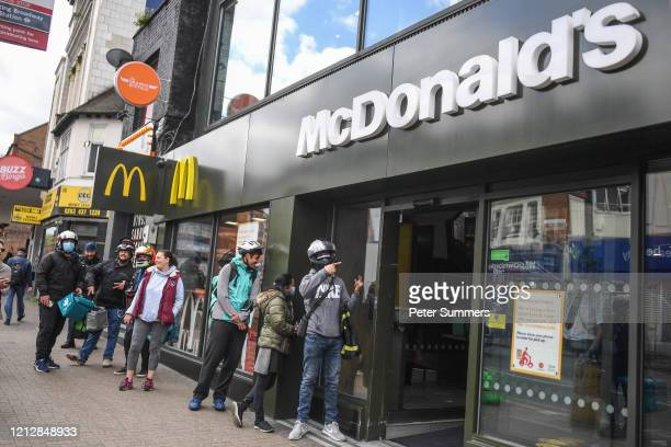 Delivery drivers are seen waiting outside a recently reopened McDonald's store in Tooting on May 13, 2020 in London, England. The prime minister...