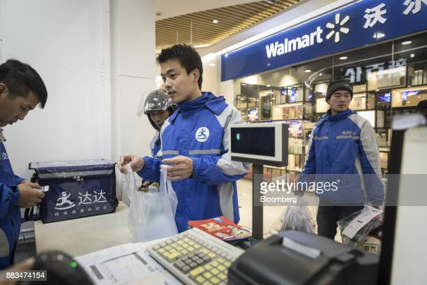 Delivery drivers assigned by JDcom Inc's Dada app collect orders outside a WalMart Stores Inc miniwarehouse for WalMart's onehour delivery service in...