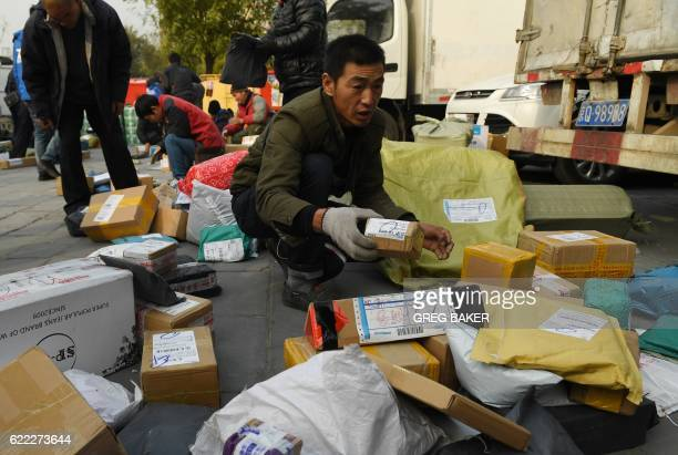 A delivery drivers prepares packages at a sorting center during the 'Double Eleven' Online Shopping Festival day in Beijing on November 11 2016...