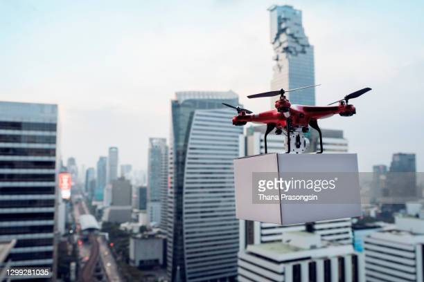 delivery drone carrying urgent shipment box in a city. - drone stock pictures, royalty-free photos & images