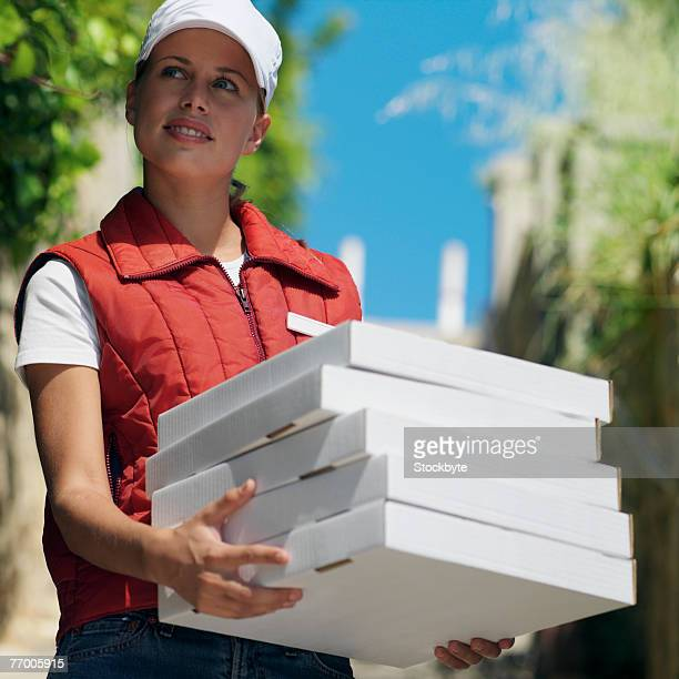 Delivery girl carrying pizza boxes outdoors, low angle view