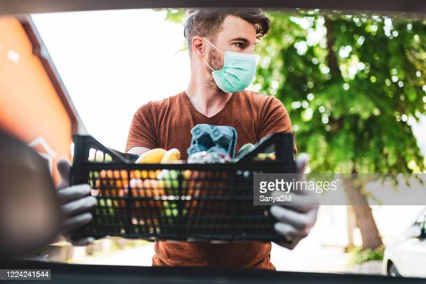 delivery guy with protective mask and gloves delivering groceries during lockdown and pandemic - volunteer stock pictures, royalty-free photos & images