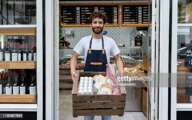 delivery man at a deli holding a box with products for a customer smiling at camera - delicatessen stock pictures, royalty-free photos & images