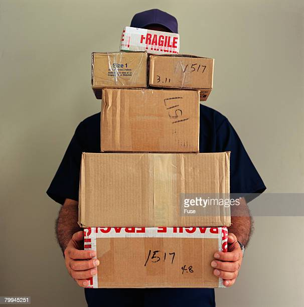 delivery man balancing boxes - excess stock photos and pictures