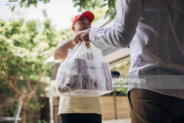 delivery man bringing food - takeout stock pictures, royalty-free photos & images