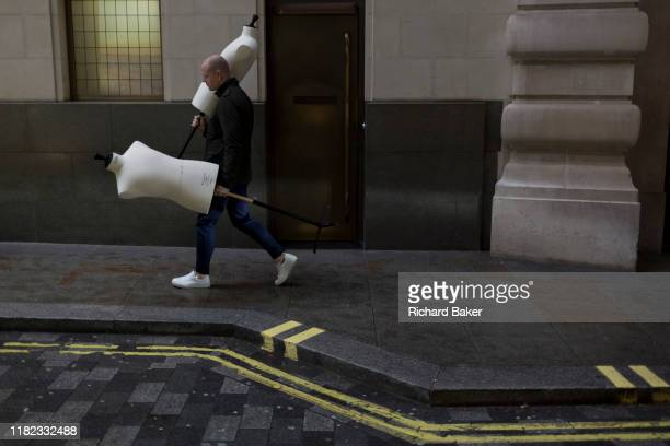 A delivery man carries a delivery of two tailor's dummies to the rear entrance of a West End retailer on 12th November 2019 in London England