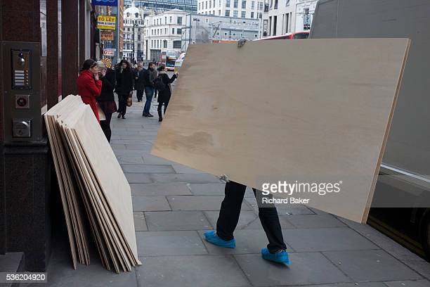 Delivery man carries the last sheet of plyboard for local construction project. Carrying the boards from a waiting white van to a pile of similars in...