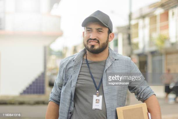 delivery man carrying a package in a residential neighborhood - pardo brazilian stock pictures, royalty-free photos & images