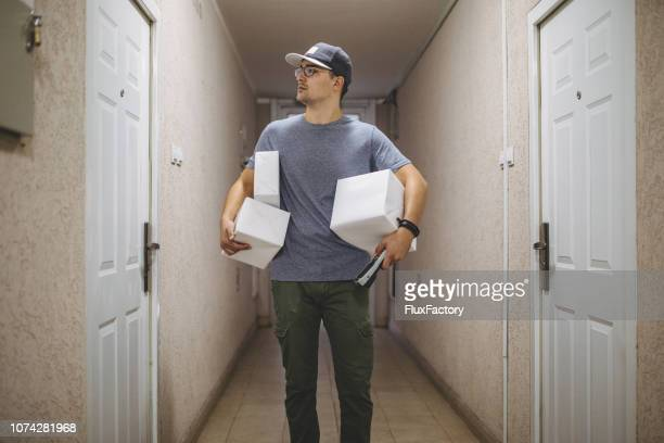 delivery man carrying boxes looking for a right address - part time job stock pictures, royalty-free photos & images