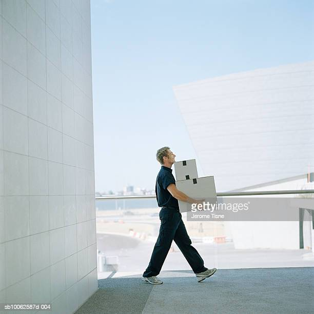 delivery man carrying boxes outside building, side view - carrying stock pictures, royalty-free photos & images
