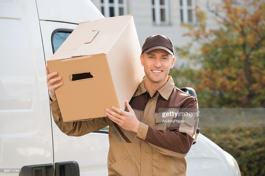 Delivery Man Carrying Cardboard Box On Shoulder : Stock-Foto
