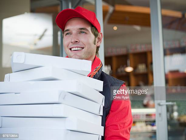 Delivery man carrying stack of pizza boxes
