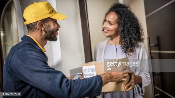 delivery man delivering package to home customer - carteiro imagens e fotografias de stock