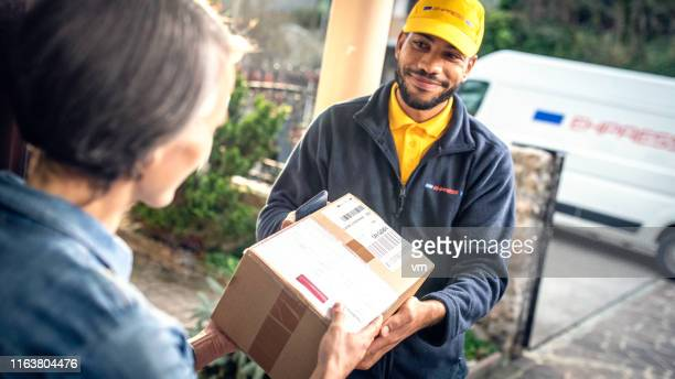 delivery man delivering package to home customer - delivery person stock pictures, royalty-free photos & images