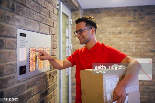 delivery man doing his job - intercom stock pictures, royalty-free photos & images