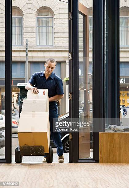 Delivery man entering a shop with boxes on a