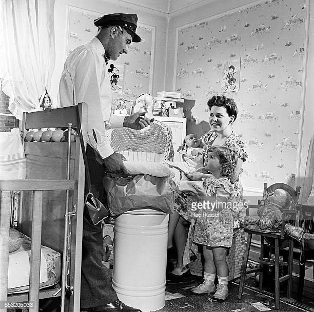 A delivery man for Crib Diaper Service delivers a set of cloth diapers to a mother and her two young children Long Island New York June 1947