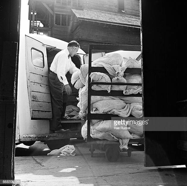 A delivery man for Crib Diaper Service unloads the day's deliveries of cloth diapers Brooklyn New York New York 1947