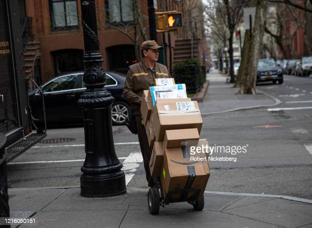 Delivery man for United Parcel Service, UPS, moves his hand truck loaded with packages through a residential neighborhood in Brooklyn, New York on...