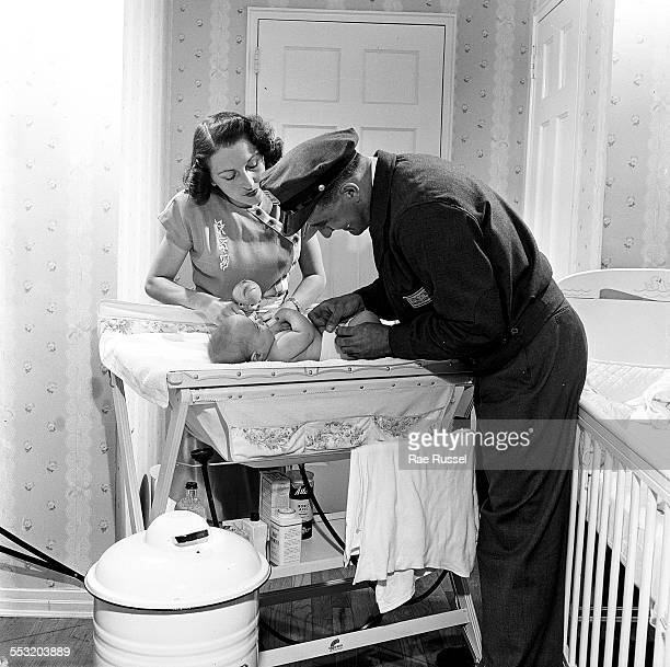 Delivery man from Crib Diaper Service changes the diaper of a young baby boy while showing a young mother how to apply the diaper, Long Island, New...