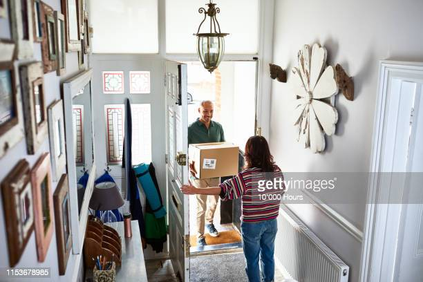 delivery man giving parcel to woman in hallway - receiving stock pictures, royalty-free photos & images