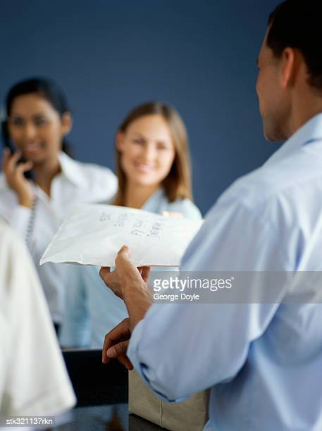 delivery man handing a parcel to a businesswoman