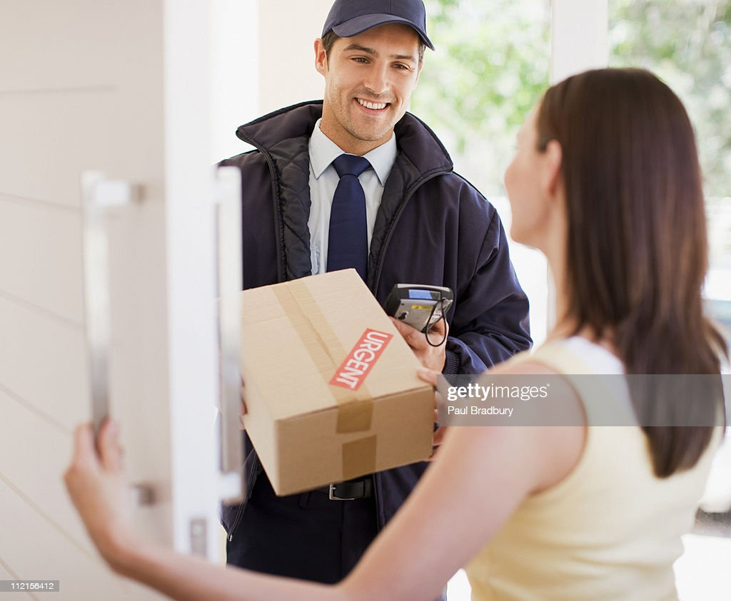 Delivery man handing box to woman : Stock Photo