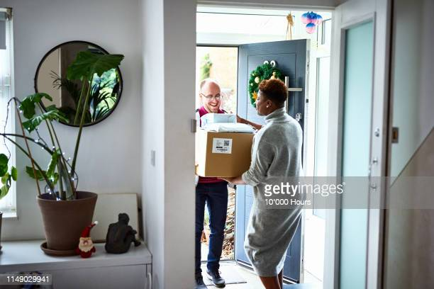 delivery man handing over cardboard box to female customer - receiving stock pictures, royalty-free photos & images