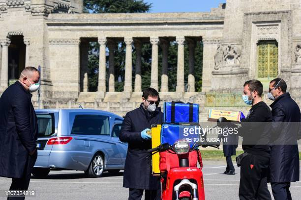 A delivery man hands boxes of pizzas for undertakers wearing a face mask to have lunch on the parking lot of the Monumental cemetery of Bergamo...