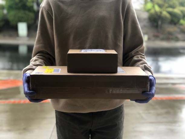 Delivery man holding boxes with gloved hands