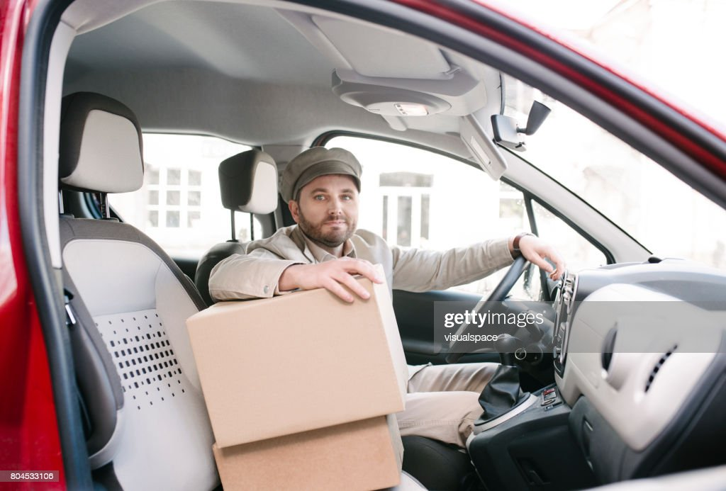 Delivery Man In Car With Bo Stock Photo | Getty Images
