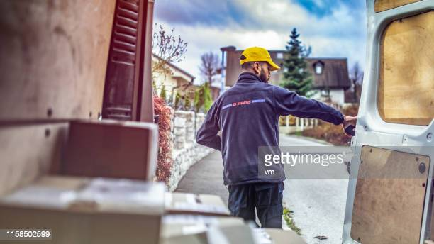 delivery man in front of a van - postal worker stock pictures, royalty-free photos & images