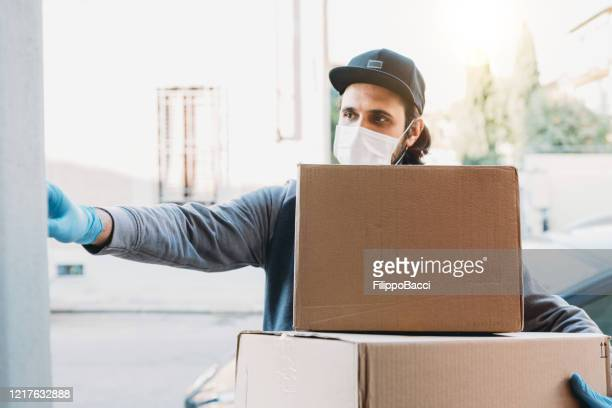 delivery man is ringing the bell to deliver two cardboard boxes - face mask protective workwear stock pictures, royalty-free photos & images
