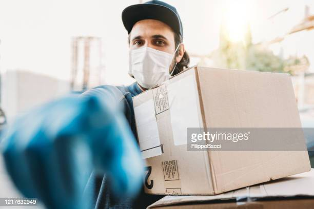 delivery man is ringing the bell to deliver two cardboard boxes - ringing doorbell stock pictures, royalty-free photos & images