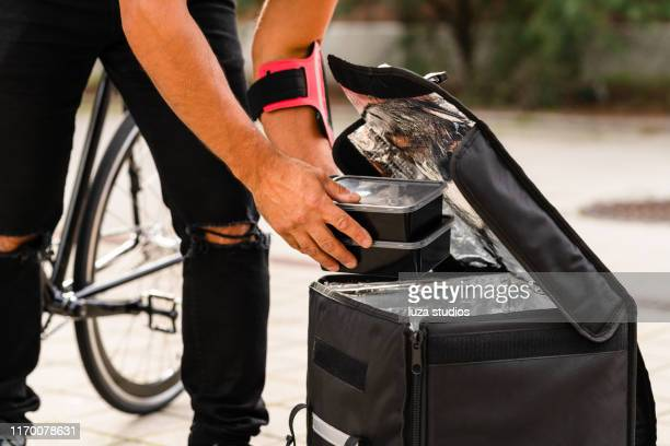 a delivery man is using a bike to transport food in the city - open backpack stock pictures, royalty-free photos & images