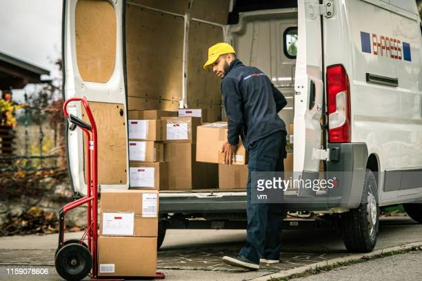 delivery man loading boxes on a push cart - delivery person stock pictures, royalty-free photos & images