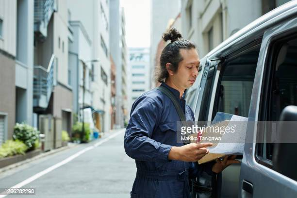 delivery man looking at a map to see where he's going to deliver - makiko tanigawa ストックフォトと画像