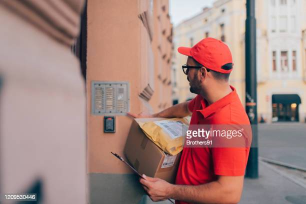 delivery man looking for the address - uniform cap stock pictures, royalty-free photos & images