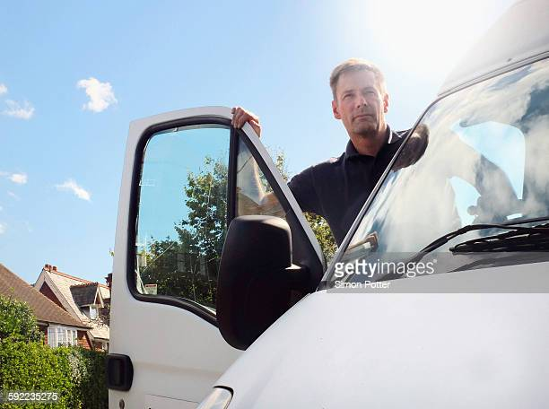delivery man looking out from white van on suburban street - mini van stock photos and pictures