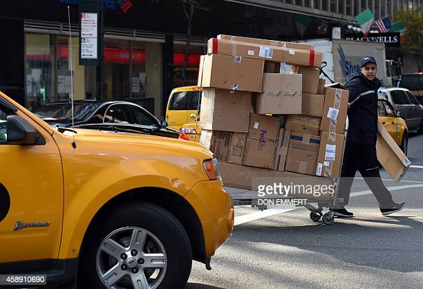 A delivery man moves boxes on a cart up 3rd Avenue on November 13 2014 in New York The man manuevered the loaded cart through heavy trafic AFP...
